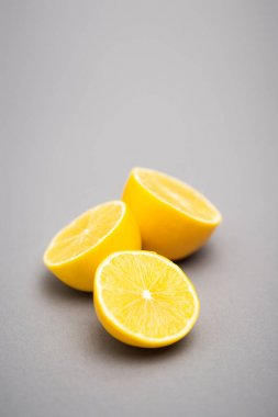 Three halves of juicy lemons on grey background stock vector