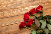 Hochwinkelaufnahme von roten Rosen auf Holzoberfläche