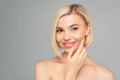 Mosolygó szőke nő alkalmazó kozmetikai krém arcán elszigetelt szürke