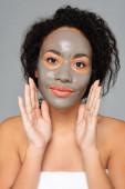 Afričanky americká žena s hliněnou maskou při pohledu na kameru izolované na šedé
