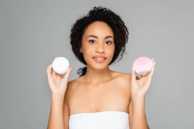 Young african american woman holding silicone cleanser and cosmetic cream isolated on grey stock vector