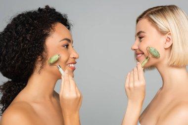 Çok ırklı kadınların birbirlerine gülümserken gri renkte yeşil bigudiler kullanmalarının yan görünüşü