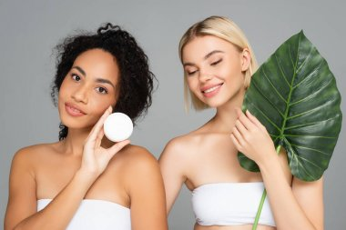 Smiling interracial women posing with cosmetic cream and tropical leaf isolated on grey stock vector