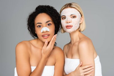 Multiethnic women with cleansing stripe and sheet mask looking at camera isolated on grey stock vector