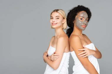 Multicultural women in facial masks and towels looking at camera isolated on grey stock vector