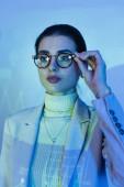 Geschäftsfrau im Anzug stellt Brille ein und schaut im Büro weg