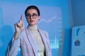 Geschäftsfrau in Anzug und Brille und zeigt mit dem Finger in die Nähe digitaler Grafiken