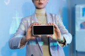 partial view of businesswoman holding smartphone with blank screen