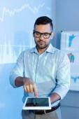 Geschäftsmann mit Brille zeigt mit Finger auf digitales Tablet mit leerem Bildschirm