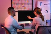 Geschäftsfrau zeigt mit dem Finger auf Computermonitor mit leerem Bildschirm neben Büromitarbeiterin
