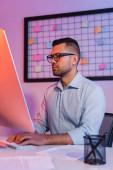 Geschäftsmann in Brille tippt auf Computertastatur und blickt auf Monitor