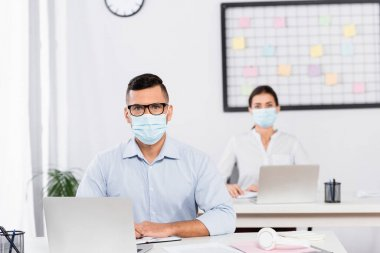 Businessman in medical mask and glasses looking at camera near businesswoman on blurred background stock vector