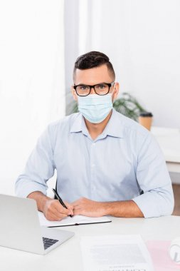 Businessman in medical mask and glasses looking at camera while holding pen near notebook and laptop on desk stock vector