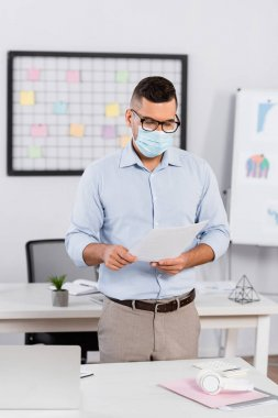 Businessman in medical mask and glasses looking at documents stock vector