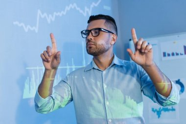 Businessman in glasses pointing with fingers near digital graphs in office stock vector