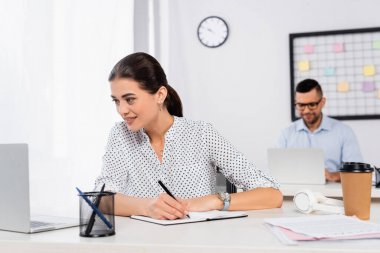 Smiling businesswoman writing in notebook near businessman on blurred background stock vector