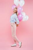 teljes hossza vidám nő álló és gazdaság lufik rózsaszín