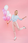 plná délka radostné ženy skákání a držení balónky na růžové
