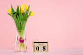 wooden calendar with 8 march lettering near vase with tulips on pink