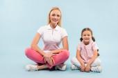 glückliche Mutter und Kind sitzend mit gekreuzten Beinen auf blauem Hintergrund