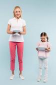 plná délka veselé matky a dcery držící digitální tablety na modré