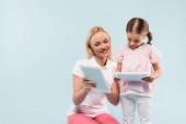šťastná matka a dcera drží digitální tablety izolované na modré