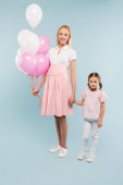full length of happy pregnant woman holding balloons near daughter on blue