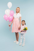 full length of happy pregnant woman holding balloons near daughter with tulips on blue
