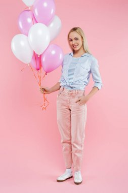 Happy woman standing with hand in pocket and holding balloons on pink stock vector