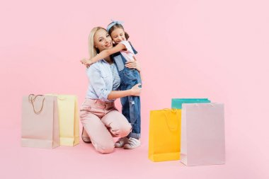 Full length of happy daughter hugging smiling mother near shopping bags on pink stock vector