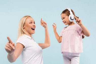 happy kid in wireless headphones dancing with cheerful mother isolated on blue