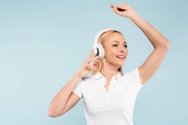 cheerful woman in wireless headphones isolated on blue