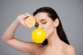 young brunette woman with makeup blowing yellow bubblegum and holding half of ripe lemon isolated on grey