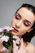 mladá žena s růžové oční stíny pohledu pryč v blízkosti květin izolovaných na šedé