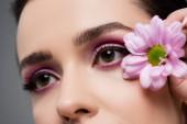 zblízka smyslné ženy s růžové oční stíny drží květiny izolované na šedé