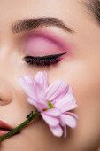 close up of sensual young woman with pink eye shadows holding flower