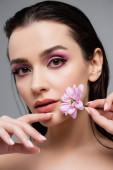 mladá smyslná žena s růžové oční stíny drží květiny izolované na šedé
