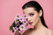 young sensual woman with bare shoulders holding flowers isolated on pink
