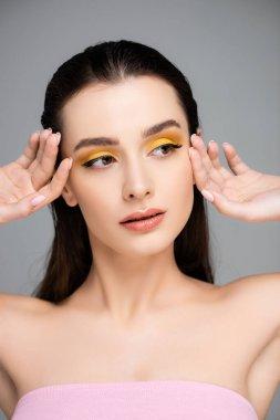 Brunette young woman with yellow eyeshadow looking away isolated on grey stock vector