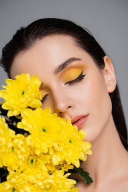 Young brunette woman with makeup near blooming yellow flowers isolated on grey stock vector