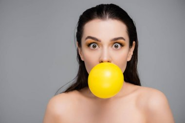 Brunette woman with makeup blowing yellow bubblegum isolated on grey stock vector