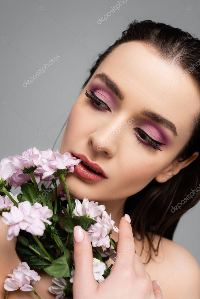 Young woman with pink eye shadows looking away near flowers isolated on grey stock vector