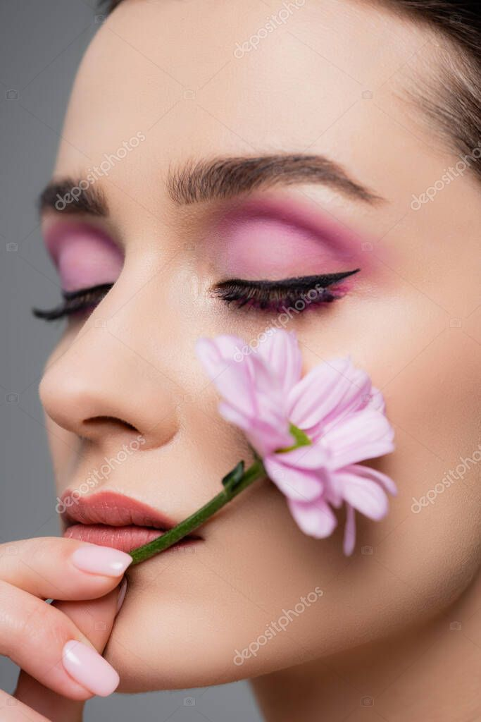 Close up of sensual woman with pink eye shadows and closed eyes holding flower isolated on grey stock vector