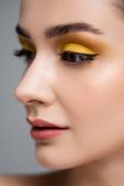 zblízka mladé ženy se žlutým očním stínem dívá pryč izolované na šedé