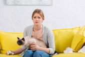 Feldúlt nő gazdaság szalvéta és sziámi macska a kanapén