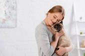 Usmívající se žena se zavřenýma očima objímající siamskou kočku