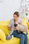 fiatal nő -val allergia holding pills és szalvéta mellett Sziámi macska