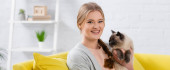 Cheerful woman smiling at camera while holding siamese cat at home, banner