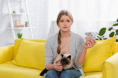 Disappointed woman with allergy reaction holding siamese cat and pills in living room