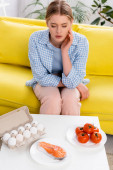 Salmon, eggs and tomatoes near woman with allergy on couch
